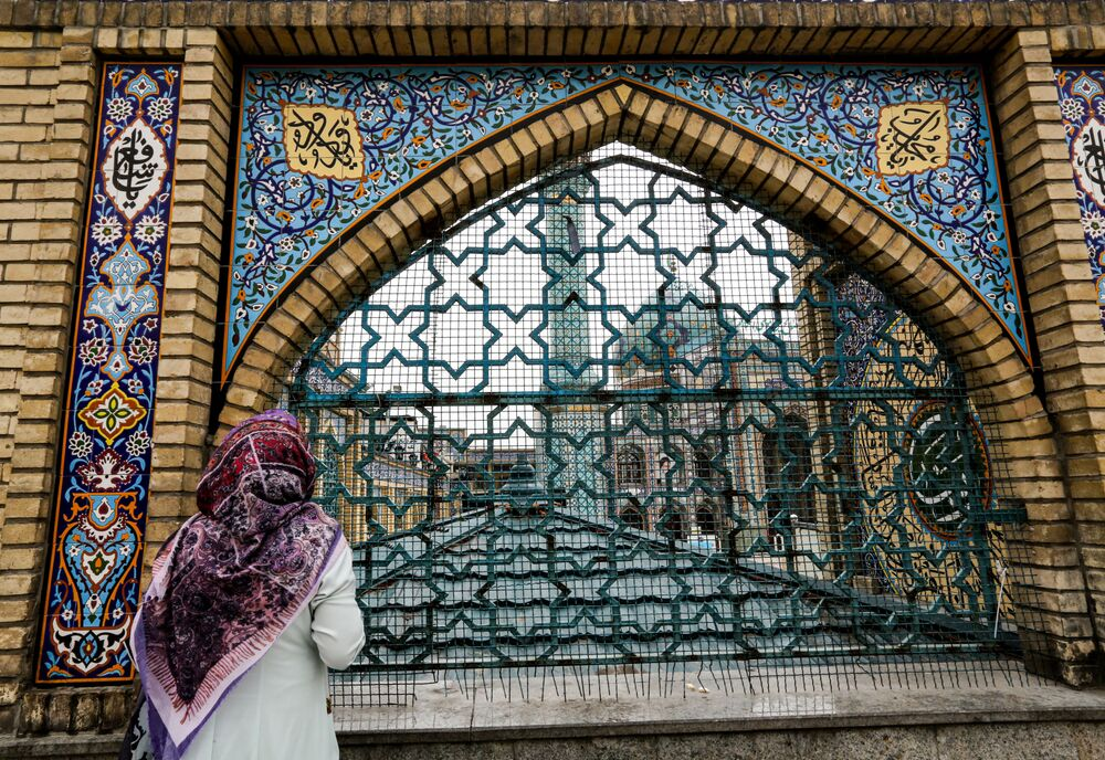 A woman stands by the fence outside the Imamzadeh Saleh in the Iranian capital Tehran's Shemiran district on 25 April 2020 during the Muslim holy month of Ramadan, as all mosques and places of worship are closed due to the COVID-19 coronavirus pandemic.