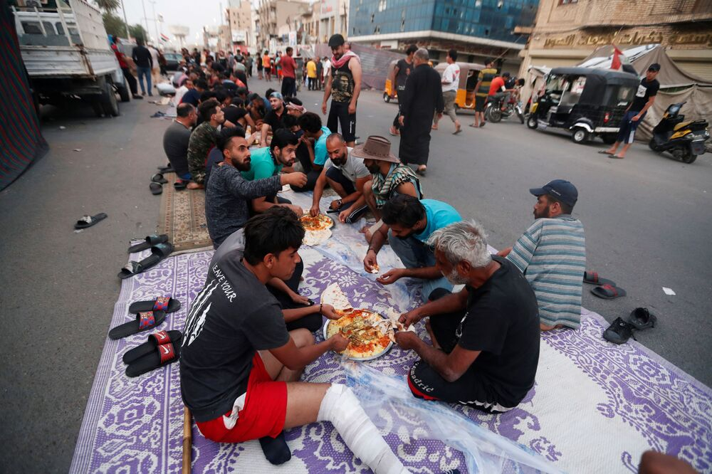 Iraqi demonstrators eat their Iftar (breaking fast) meals during the holy month of Ramadan as anti-government protests continue at Tahrir Square, in Baghdad, Iraq 25 April 2020.