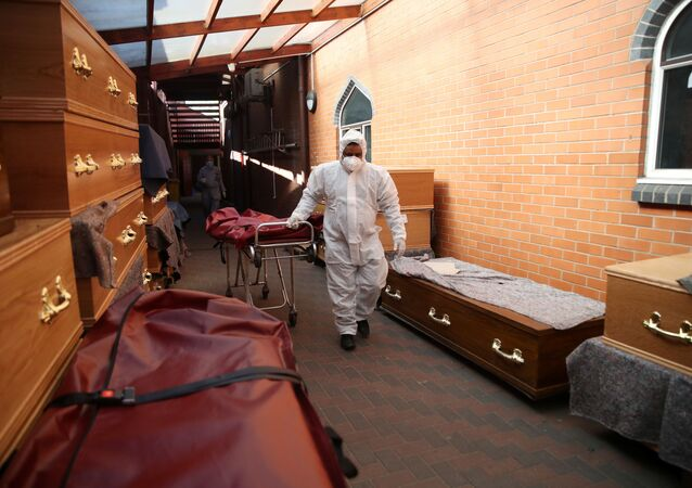 A worker wearing protective equipment is seen by coffins at a temporary coronavirus morgue set up at a mosque in Birmingham.