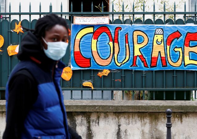 FILE PHOTO: A man wearing a protective mask walks past a sign that reads Courage, in Paris as a lockdown is imposed to slow the rate of the coronavirus disease (COVID-19) in France, April 25, 2020