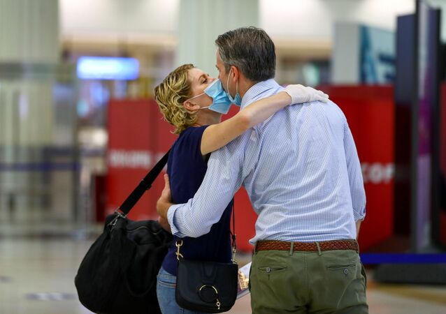 A man wearing a protective mask kisses his wife before she boards a plane at Dubai International Airport, as Emirates airline resumed limited outbound passenger flights amid the COVID-19 pandemic in Dubai, UAE, 27 April 2020