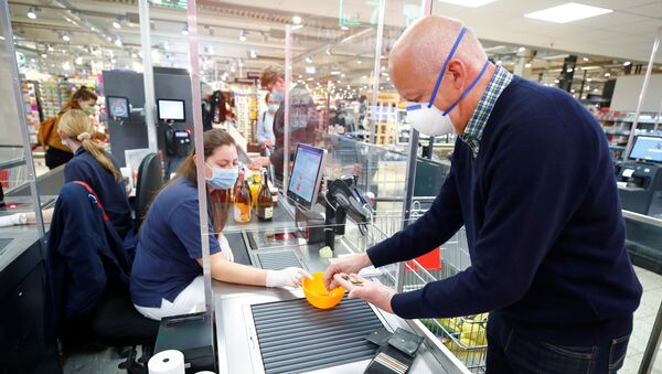 A man wearing a face mask pays at the checkout in a supermarket, after the federal state of North Rhine-Westphalia decided to make wearing protective masks obligatory in shops and public transportation to fight the spread of the coronavirus disease (COVID-19), in Bad Honnef near Bonn,  Germany, April 27, 2020. - Sputnik International