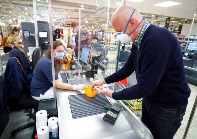 A man wearing a face mask pays at the checkout in a supermarket, after the federal state of North Rhine-Westphalia decided to make wearing protective masks obligatory in shops and public transportation to fight the spread of the coronavirus disease (COVID-19), in Bad Honnef near Bonn,  Germany, April 27, 2020.