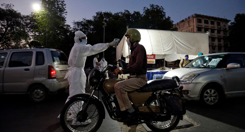 A health worker uses an infrared thermometer to measure the temperature of a motorcyclist on a road in India