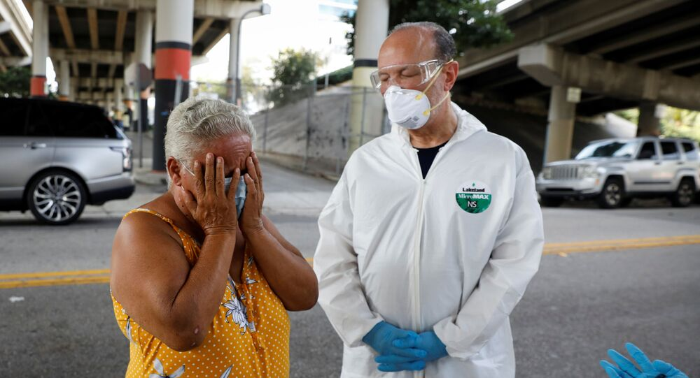 A homeless woman reacts next to a worker collecting samples during a Miami-Dade County testing operation for the coronavirus disease (COVID-19), in downtown Miami, Florida, U.S., April 16, 2020