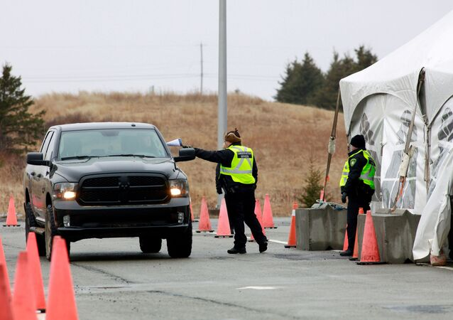 A Nova Scotia conservation officer passes a paper to a person crossing into the province from New Brunswick in its effort to prevent the spread of the coronavirus disease (COVID-19) at the Fort Lawrence, Canada April 2, 2020.