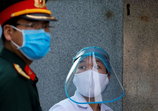 A health worker wears a protective face shield next to a soldier as they work at the quarantined Nephrology hospital during the coronavirus disease (COVID-19) outbreak in Hanoi, Vietnam April 14, 2020