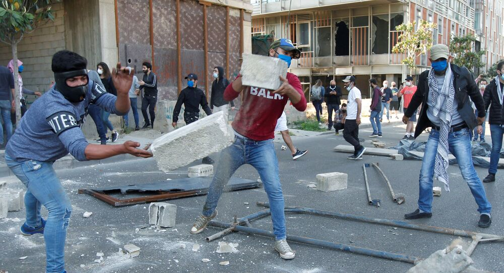 Demonstrators throw pieces of concrete during a protest against growing economic hardship in Beirut, Lebanon April 28, 2020