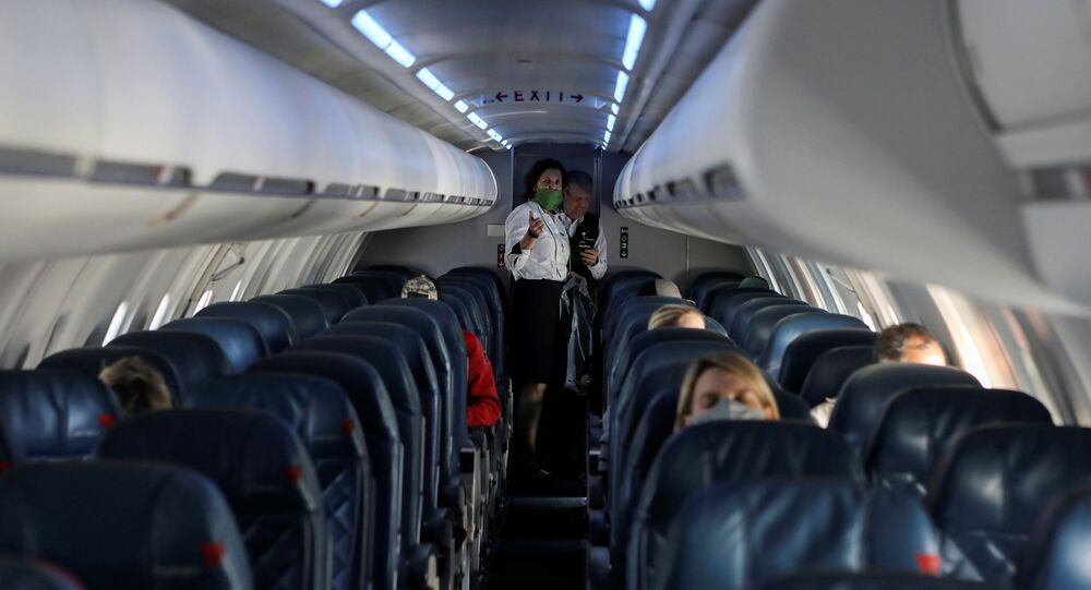 Flight attendants talk in a nearly empty cabin on a Delta Airlines flight operated by SkyWest Airlines as travel has cutback, amid concerns of the coronavirus disease (COVID-19), during a flight departing from Salt Lake City, Utah, U.S. April 11, 2020.