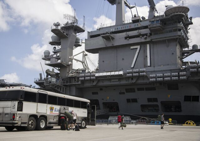 Sailors assigned to the aircraft carrier USS Theodore Roosevelt (CVN 71) prepare to embark the ship after weeks of cleaning and essential watch standing