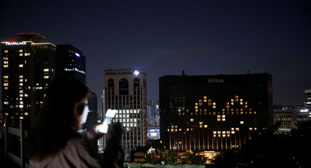 A woman wearing a protective face mask uses her phone as the Millennium Hilton Hotel lights up its rooms in the shape of a smiling emoji to comfort people amid the coronavirus disease (COVID-19) outbreak in Seoul, South Korea, April 26, 2020.