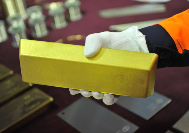 A worker holds a gold bar.