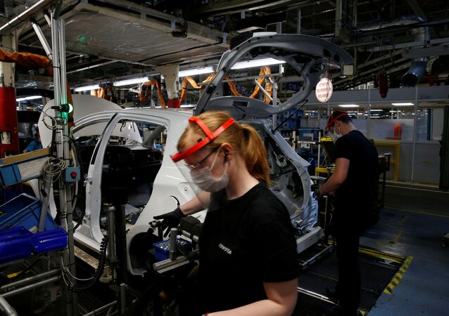 Employees wearing protective face masks work on the automobile assembly line at the Toyota Motor Manufacturing France plant as it resumes its operations after five weeks of closure during a lockdown amid the coronavirus disease (COVID-19) outbreak, in Onnaing, France, April 23, 2020