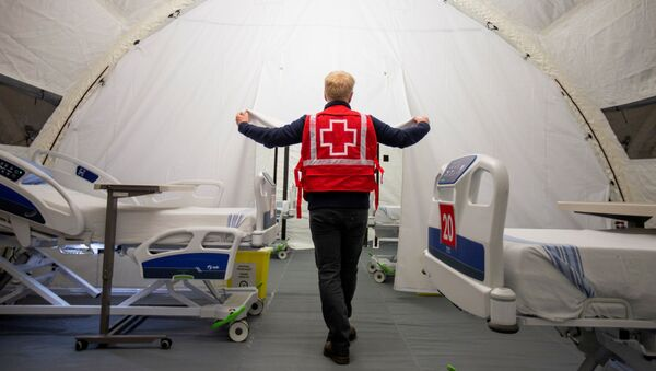 FILE PHOTO: A volunteer with the Red Cross shows a doorway between beds in a mobile hospital set up in partnership with the Canadian Red Cross in the Jacques-Lemaire Arena to help care for patients with the coronavirus disease (COVID-19) from long-term centres (CHSLDs), in Montreal, Quebec, Canada April 26, 2020 - Sputnik International