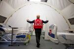 FILE PHOTO: A volunteer with the Red Cross shows a doorway between beds in a mobile hospital set up in partnership with the Canadian Red Cross in the Jacques-Lemaire Arena to help care for patients with the coronavirus disease (COVID-19) from long-term centres (CHSLDs), in Montreal, Quebec, Canada April 26, 2020