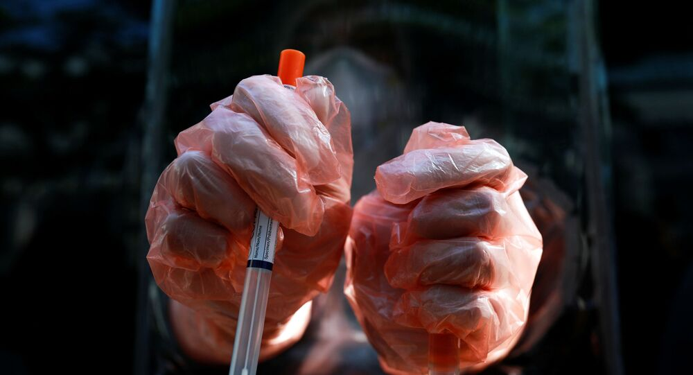 A medic wearing protective gloves shows a test kit as he works at a mobile laboratory for coronavirus disease (COVID-19) testing in Bangkok, Thailand, April 9, 2020.