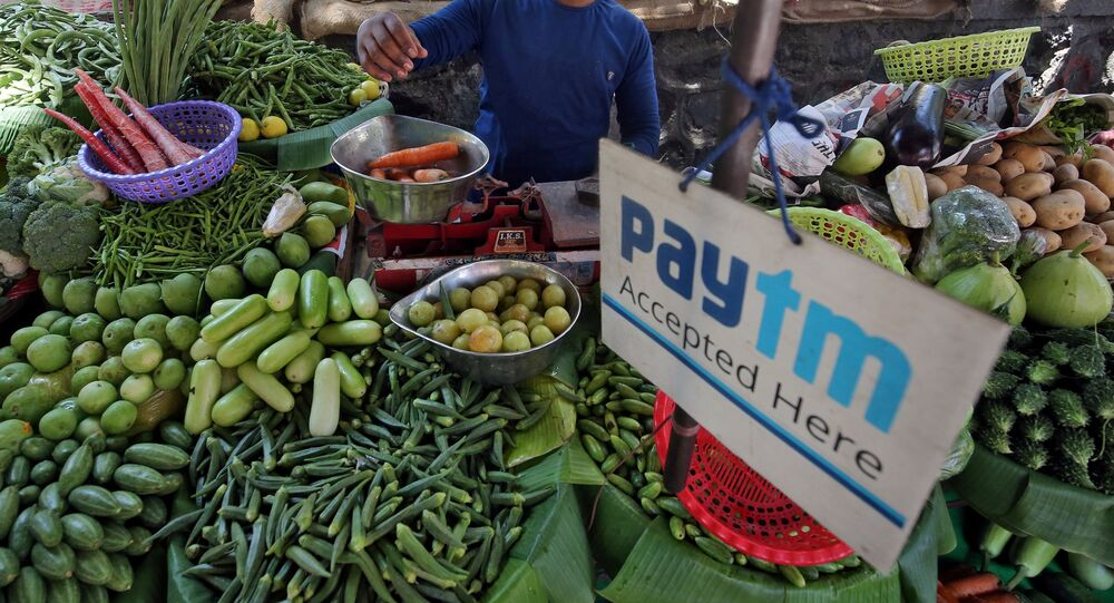 FILE PHOTO: A vendor weighs vegetable next to an advertisement of Paytm, a digital payments firm, hanging amidst his vegetables at a roadside market in Mumbai, India, April 2, 2019