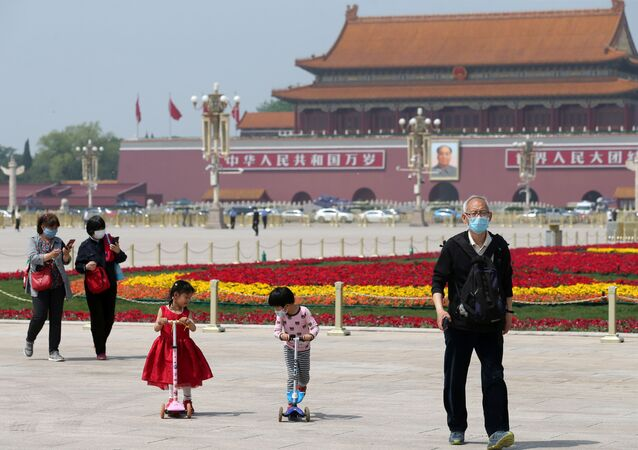 People wearing face masks following the coronavirus disease (COVID-19) outbreak walk past flower installations set up to mark the upcoming Labour Day holiday, at Tiananmen Square in Beijing, China, 29 April 2020