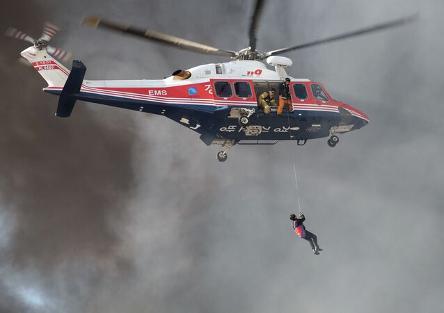 A resident (bottom) is surrounded by smoke as he is winched up to a rescue helicopter from an apartment building which caught fire in Uijeongbu, north of Seoul, on January 10, 2015