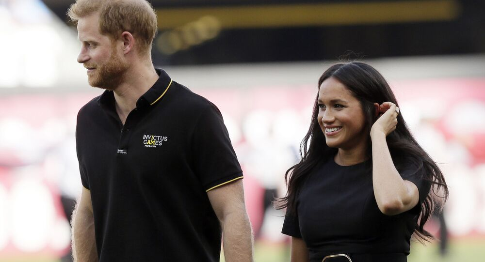 Britain's Prince Harry, and his wife Meghan, Duchess of Sussex, walk off the field before a baseball game in London.