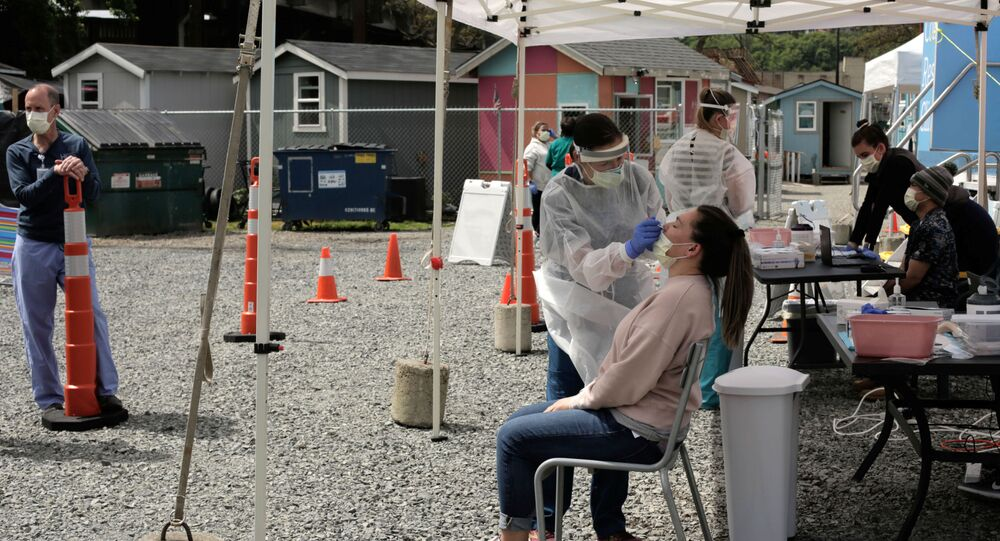 Physician Lauren Bernese administers a test for coronavirus disease (COVID-19) to Rachael Benson, a case manager at Interbay Village, a village of tiny houses managed by the Low Income Housing Institute, in Seattle, Washington, U.S. April 29, 2020