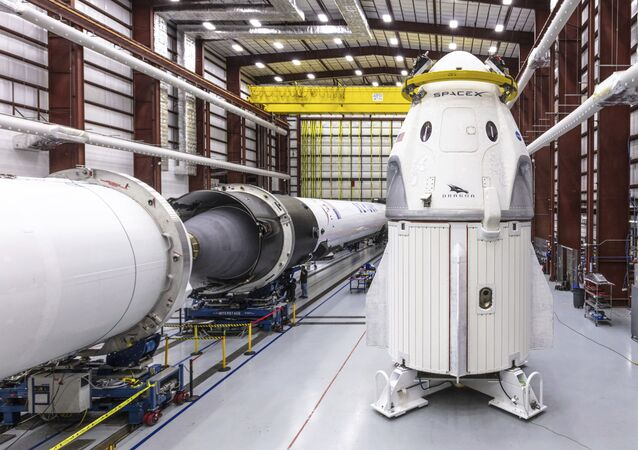 In this Dec. 18, 2018 photo provided by SpaceX, SpaceX's Crew Dragon spacecraft and Falcon 9 rocket are positioned inside the company's hangar at Launch Complex 39A at NASA's Kennedy Space Center in Florida, ahead of the Demo-1 unmanned flight test