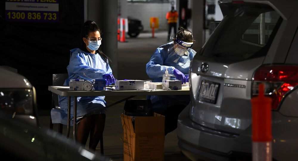 Medical staff take down details after performing tests for the COVID-19 coronavirus on people who used a drive-through testing site in a Melbourne carpark on May 1, 2020