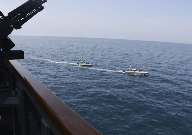 In this Wednesday, April 15, 2020, photo made available by U.S. Navy, Iranian Revolutionary Guard vessels sail close to U.S. military ships in the Persian Gulf near Kuwait