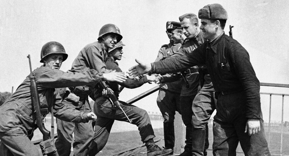 US and Soviet troops meet on the wrecked bridge over the Elbe River at Torgau, Germany on 26 April 1945