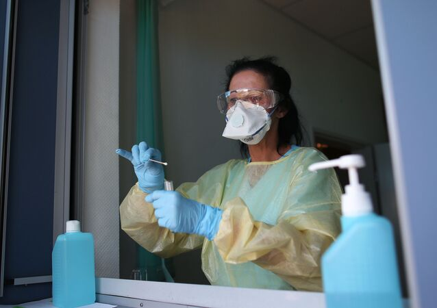 Nurse Sylke Pflugmacher takes a sample at a testing point for medical staff members at the community hospital in Magdeburg, eastern Germany, on 16 April 2020 during the novel coronavirus COVID-19 pandemic.