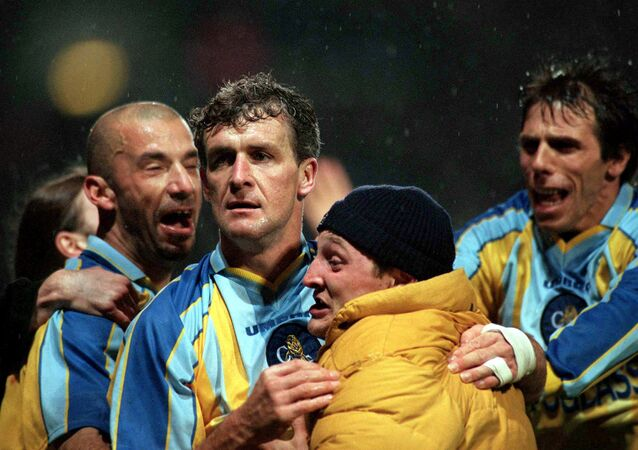 Chelsea's Mark Hughes is mobbed by player-manager Gianluca Vialli, Gianfranco Zola and a supporter