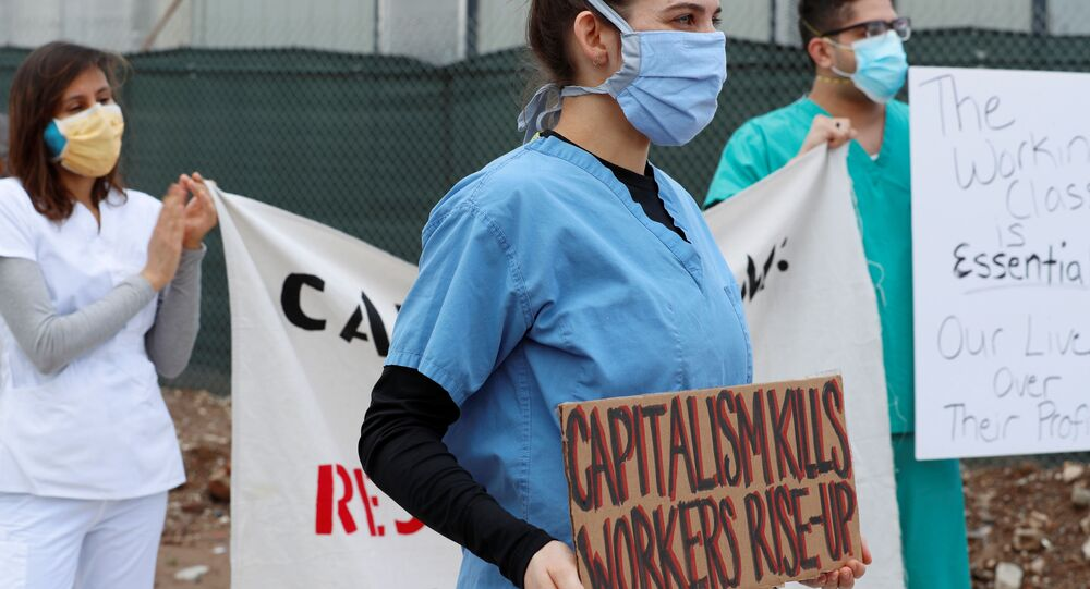Demonstrators identifying themselves as health care workers hold banners during a protest outside of an Amazon warehouse as the outbreak of the coronavirus disease (COVID-19) continues in the Staten Island borough of New York U.S., May 1, 2020. REUTERS/Lucas Jackson