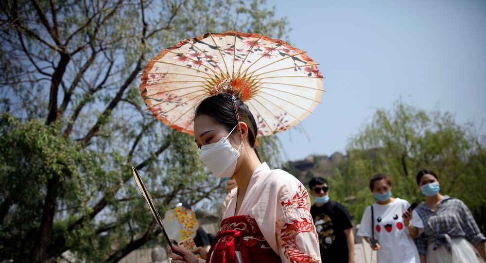 A woman wearing face mask and traditional Chinese clothing visits Gubei Water Town on the first day of the five-day Labour Day holiday, following the coronavirus disease (COVID-19) outbreak, on the outskirts of Beijing, China, May 1, 202