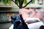 A protestor holds up a flare during a demonstration on May Day, amid the spread of the coronavirus disease (COVID-19), in Berlin, Germany May 1, 2020