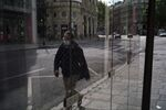 A man wears a face mask to protect against the spread of the new coronavirus as he walks in a street of Paris, Wednesday, April 29, 2020. France continues to be under an extended stay-at-home order until May 11 in an attempt to slow the spread of the COVID-19 pandemic.