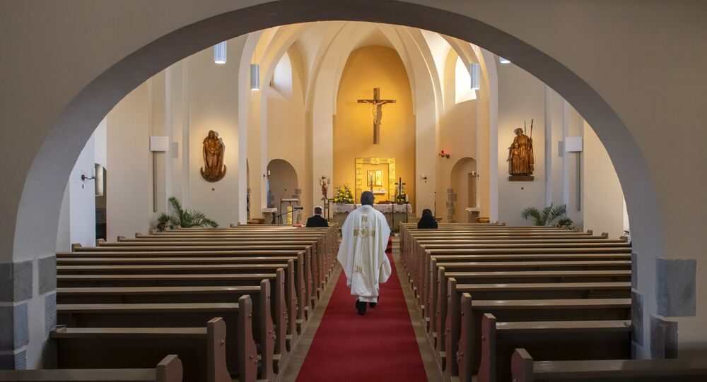 A Catholic priest celebrates a mass in the empty Church of Saint Catherine in Ralbitz, eastern Germany, Sunday, 12 April 2020.