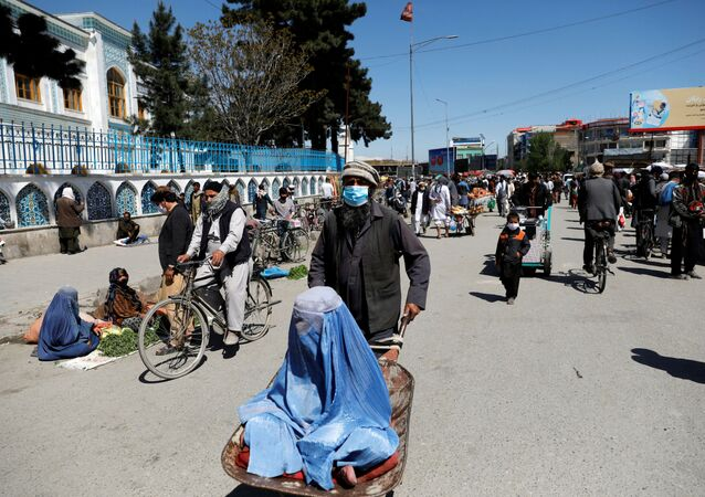 An Afghan woman sits in a handcart