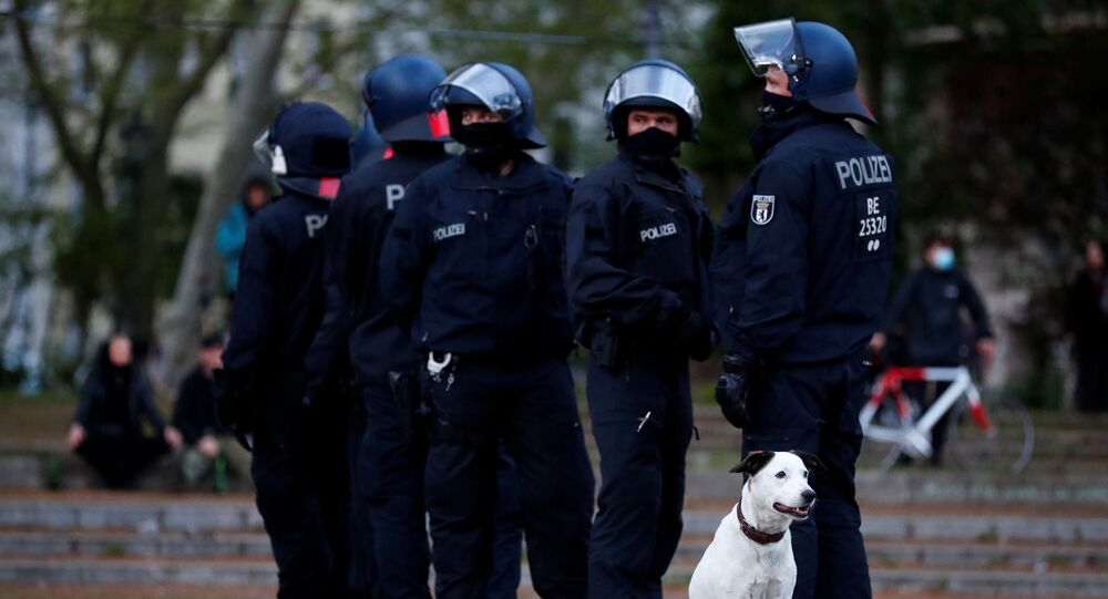 Police officers gather next to a dog during a demonstration on May Day, amid the spread of the coronavirus disease (COVID-19), in Berlin, Germany May 1, 2020