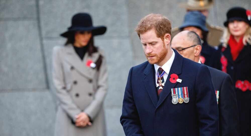 Britain's Prince Harry and his fiancee Meghan Markle, background attend an Anzac Day dawn service, at Hyde Park Corner in London, Wednesday, April 25, 2018