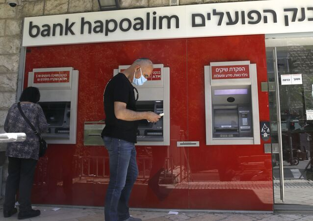 An Israeli man stands next to a Bank Hapoalim cashpoint in Jerusalem on 1 May 2020.