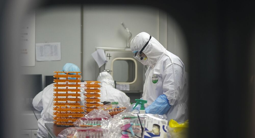 This 22 February 2020 photo released by Xinhua News Agency shows medical workers in protective suits at a coronavirus detection lab in Wuhan in central China's Hubei Province.