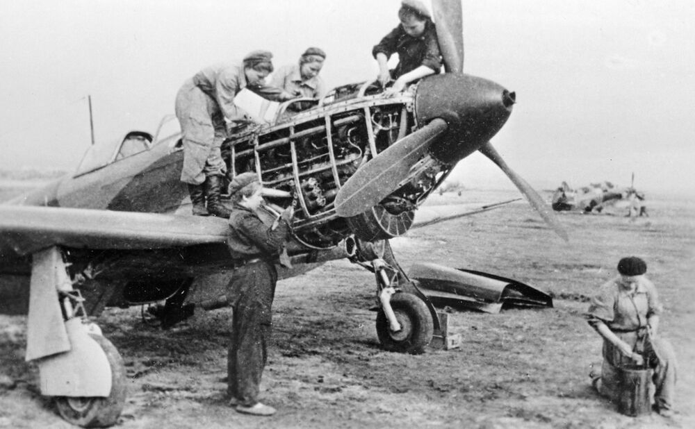 Technicians of the 586th Fighter Aviation Regiment check a plane before a flight on 30 September 1943