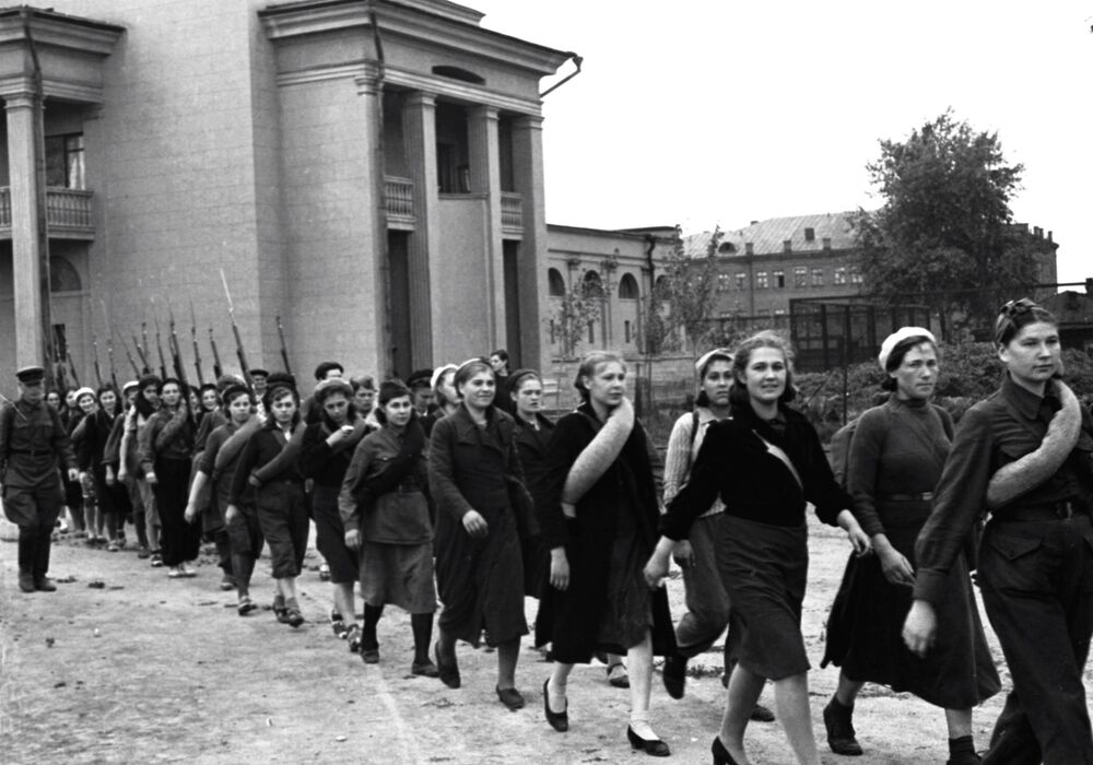 Female participants of the compulsory military training program walk along a street in Moscow on 31 August 1941