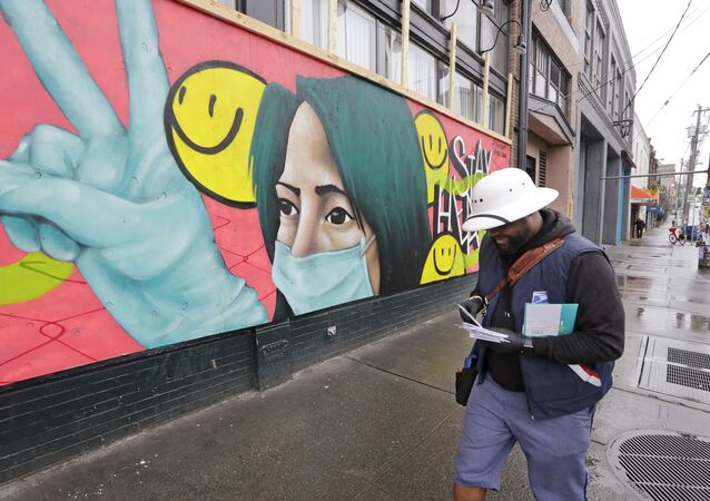 A postal carrier walks past a mural on a business closed during the coronavirus outbreak Saturday, May 2, 2020, in Seattle.