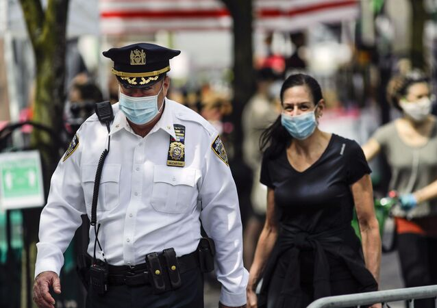 A police officer wears a protective mask as he walks among people at the Union Square GreenMarket Saturday, May 2, 2020, in New York