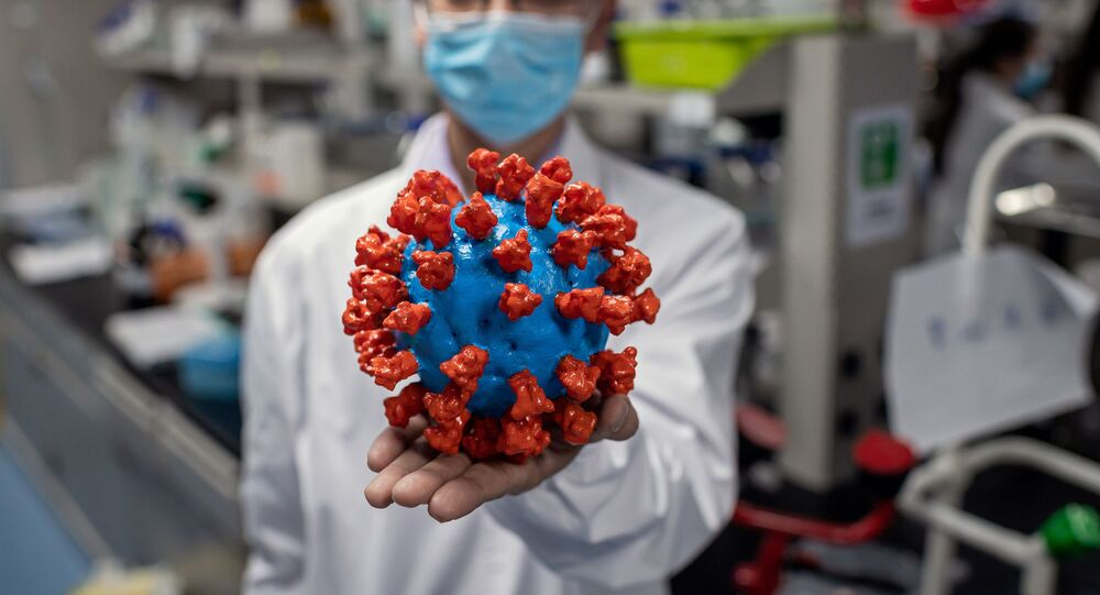 In this picture taken on 29 April 2020, an engineer shows a plastic model of the COVID-19 coronavirus at the Quality Control Laboratory at the Sinovac Biotech facilities in Beijing. Sinovac Biotech, which is conducting one of the four clinical trials that have been authorised in China, has claimed great progress in its research and promising results among monkeys.