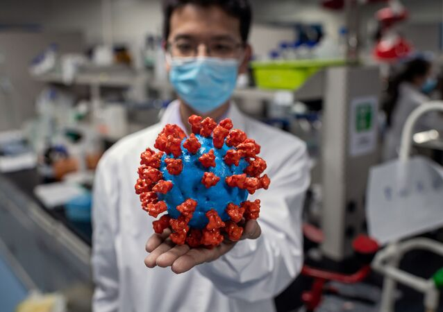 In this picture taken on April 29, 2020, an engineer shows a plastic model of the COVID-19 coronavirus at the Quality Control Laboratory at the Sinovac Biotech facilities in Beijing. - Sinovac Biotech, which is conducting one of the four clinical trials that have been authorised in China, has claimed great progress in its research and promising results among monkeys.