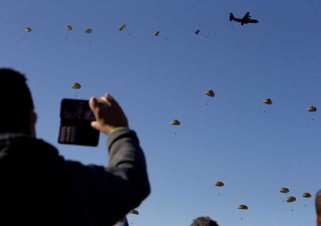 Spectators watch a mass parachute drop at Ginkel Heath, eastern Netherlands, Saturday, Sept. 21, 2019, as part of commemorations marking the 75th anniversary of Operation Market Garden, an ultimately unsuccessful airborne and land offensive that Allied leaders hoped would bring a swift end to World War II by capturing key Dutch bridges and opening a path to Berlin.