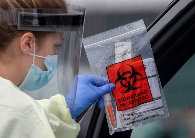 A health worker in protective gear hands out a self-testing kit in a parking lot of Rose Bowl Stadium during the global outbreak of the coronavirus disease (COVID-19), in Pasadena, California, U.S., April 8, 2020.