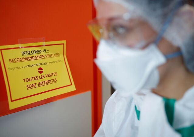 A nurse, wearing protective gear and face mask, walks past an information sign at the post COVID-19 unit of the Clinique Breteche private hospital in Nantes during the outbreak of the coronavirus disease (COVID-19) in France, April 30, 2020.